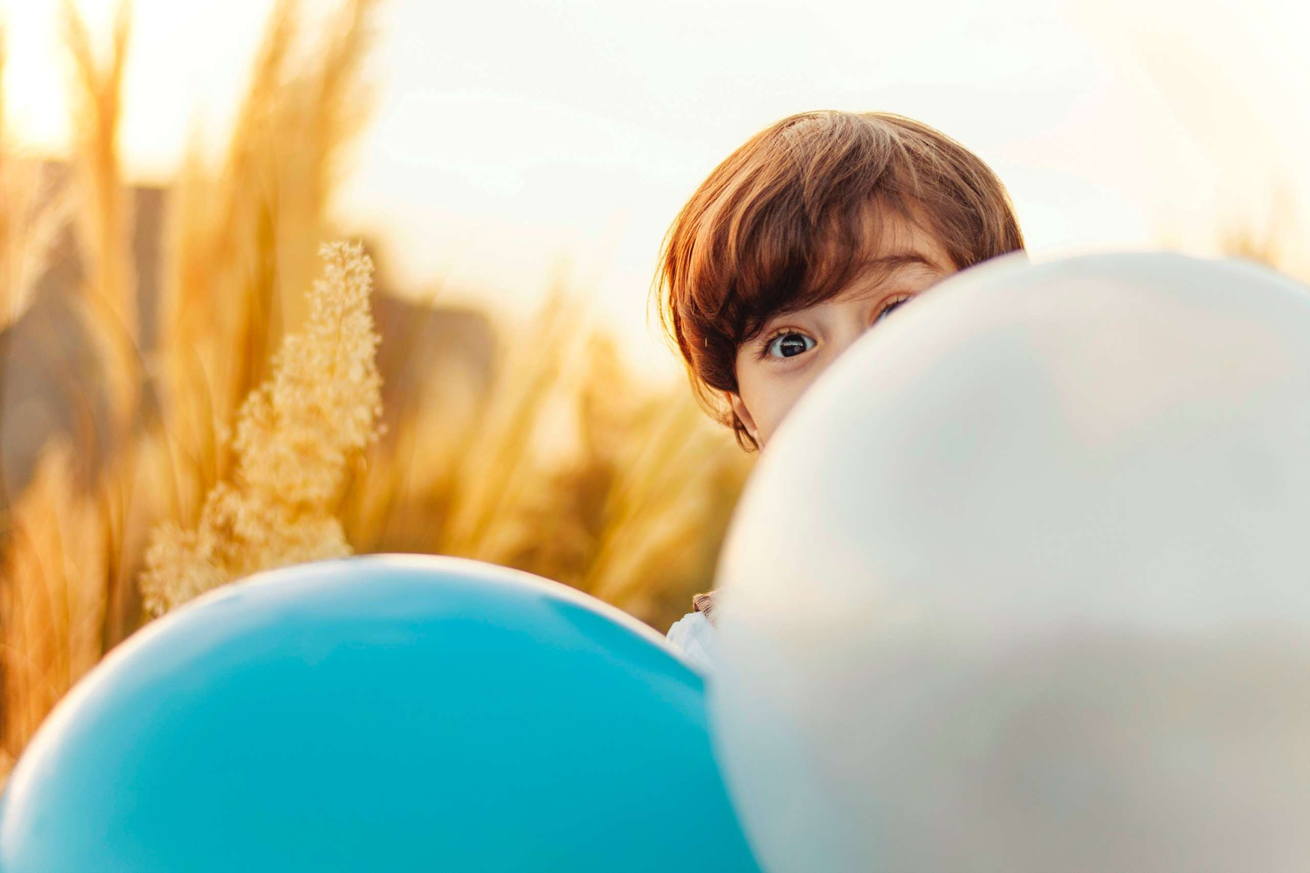 a boy looking from behind balloons
